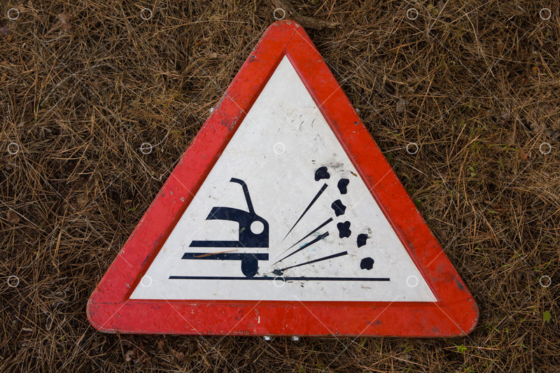 Triangle Traffic Sign For Gravel Isolated Over Dry Grassy