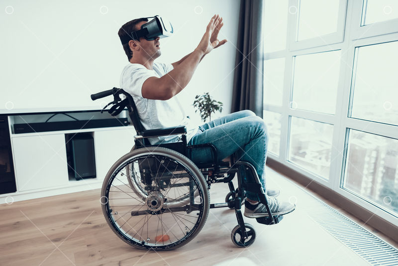 Handicapped Man in Wheelchair Wearing VR Headset Portrait of Male Disabled  Person in Casual Clothes Sitting Near Window in Large Bright Room and  Enjoying Virtual Reality Glasses and Keeping Hands Up Image -