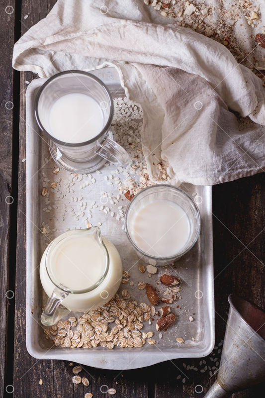 Set of non-dairy milk (rice milk, almond milk and oat milk) in glass cups  and